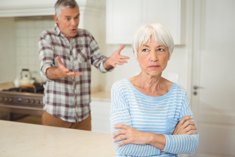 Older man and woman arguing in a white kitchen