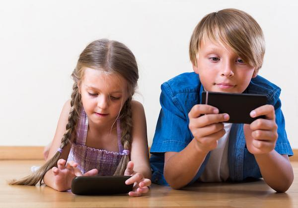 Two children playing with cell phones