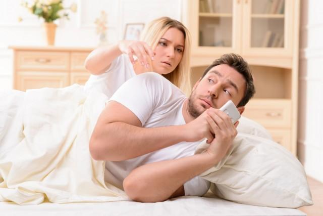 wife in bed with husband distracted by social media