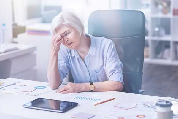 Older woman at a desk holding her forehead, distressed over finances.