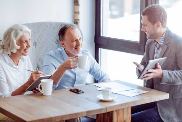 Older couple smiling having coffee with their divorce attorney