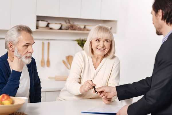 Older man and woman with their layer, signing a divorce agreement.