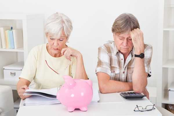 Bright pink piggy bank sits in front of an older couple each engrossed in thought.