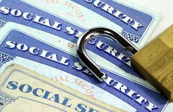 Overlapping social security cards with an open padlock on top.